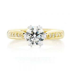 An elegant ring featuring a white gold six claw round brilliant cut diamond centre with a grain set yellow gold band.