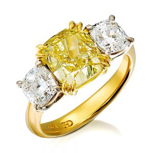 Fancy yellow diamond is balanced by two white diamonds spreading gently across the finger