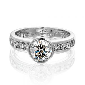 Solitaire engagement ring with bezel set round brilliant cut diamond and channel set diamond band.