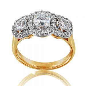 Platinum and 18 karats yellow gold cluster ring with three cushion-cut diamonds and small round brilliant cut diamonds.