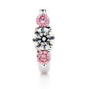 Half bezel brilliant cut diamond ring accompanied by two small round brilliant cut pink diamonds